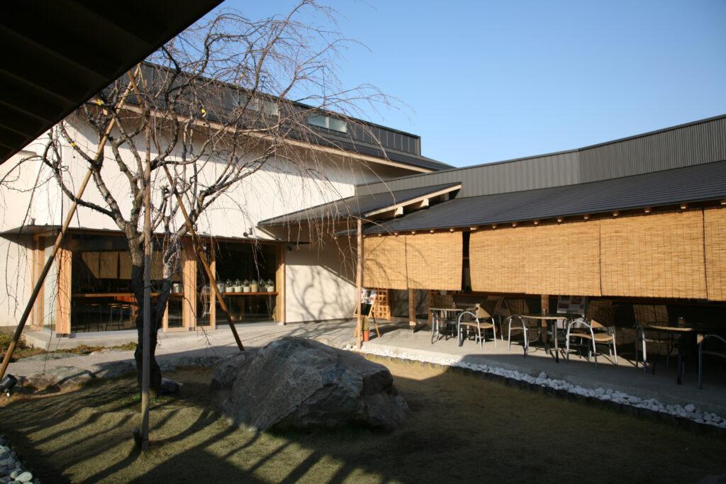 桜の木とお子さんも遊べる中庭、中央には職人さんの手焼き工房を見学できるスペース